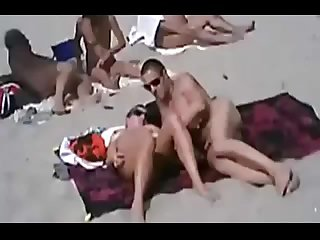 Pretty blonde lies on the beach with her mature lover & makes sex