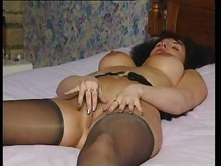 Шикарная голая мамочка в чулках мастурбирует на кровати