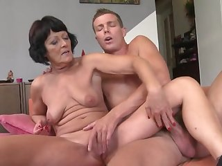 Молодой пацан на диване ебет и доводит до оргазма ненасытную старую бабу