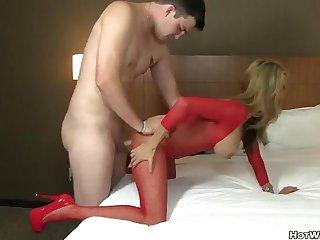 Опытная шлюха в красном обтягивающем наряде дает пацану в номере отеля