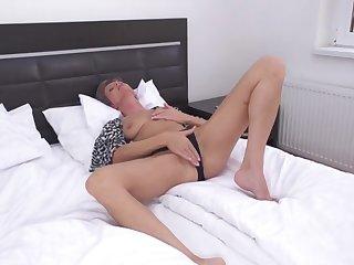 Одинокая голая мадам на кровати страстно ласкает рукой бритую киску
