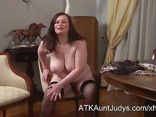 Зрелая толстушка на столе раздвинула ноги и мастурбирует волосатую пизду