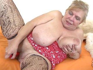 Толстая старуха развесила свои зрелые сиськи и трогает рукой набухший клитор