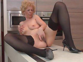 Рыжая хозяйка в чёрных чулках мастурбирует пизду на кухне пока муж был на работе
