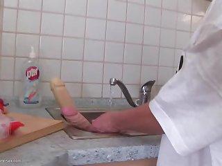 Любопытная старуха сует длинный огурец в свою волосатую пизду на кухне
