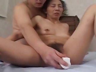 Китайскую бабку трахают вибратором в мохнатую пизду перед камерой