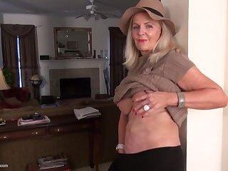 Пожилая баба в шляпе трахает себя игрушкой в киску, испытывая оргазм