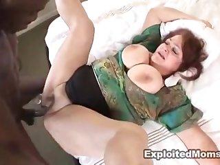 Негр ритмично потрахивает в постели толстую 60 летнюю бабу в мохнатую пизду