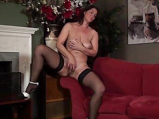Зрелая мастурбирует свою голодающую киску на красном диване