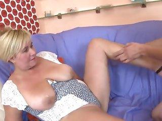 Молодой пацан страстно ласкает руками зрелые сиськи сочной матюрки на диване