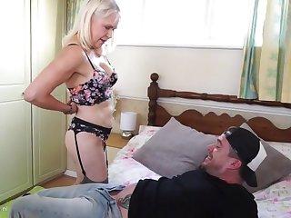 Одинокая мамаша в чулках соблазняет парня в спальне своими возбуждающими формами