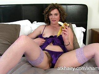 Кудрявая женщина с бананом мастурбирует киску, потягивая за волосы