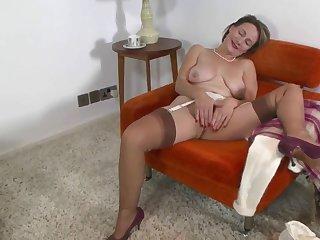 Старая хозяйка без мужика похотливо пихает два пальца в киску, сидя на кресле