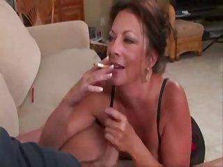 Зрелая женщина покуривая, делает минет