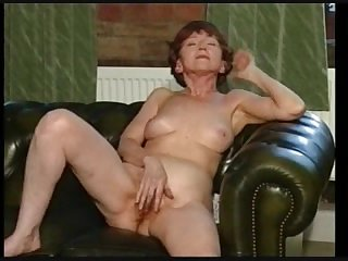 Зрелая старуха позирует на диване